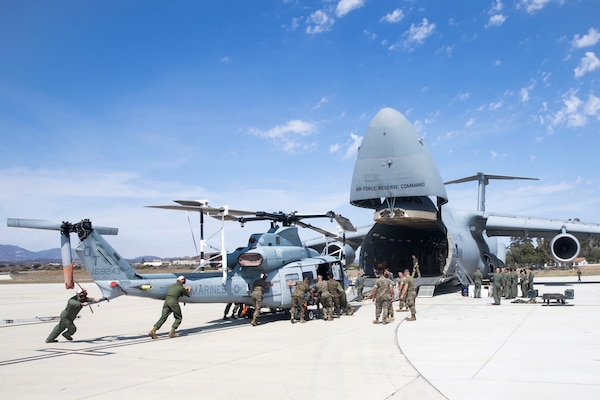 U.S. Marines and airmen assist in loading a UH-1Y Venom into C-5M Super Galaxy at Marine Corps Air Station Camp Pendleton, California, Sept. 16. The C-5M was a visiting U.S. Air Force aircraft from 433rd Airlift Wing at Joint Base San Antonio-Lackland, Texas, and was here as part of a dual service training exercise. The air station provides the 1st Marine Expeditionary Force and 3rd Marine Aircraft Wing with flexible deployment options.