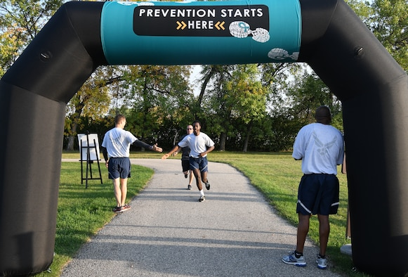 Airmen and family members from the 319th Reconnaissance Wing begin a Suicide Awareness 5K Sept. 20, 2019, on Grand Forks Air Force Base, North Dakota. Squadrons and flights were encouraged to attend the 5K in groups wearing their morale shirts and carrying unit guidons. (U.S. Air Force photo by Airman 1st Class Brody Katka)