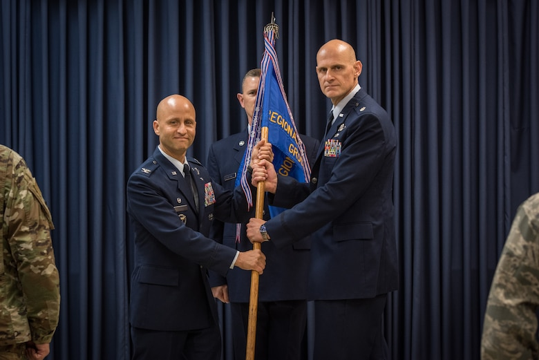U.S. Air Force Col. Terrence Koudelka, left, the commander of the 193rd Special Operations Wing, Pennsylvania Air National Guard, passes a guidon to Lt. Col. Kristian Post, the commander of the 193rd Regional Support Group, during an assumption of command ceremony.