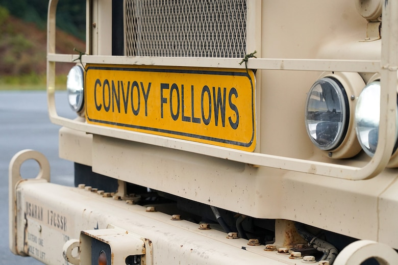 A 'convoy follows' sign is seen attached to the front of an M415A5 tractor during a rest stop as Soldiers assigned to the 109th Transportation Company, 17th Combat Support Sustainment Battalion, U.S. Army Alaska, drive through the Kenai Penninsula to load U.S. Marine Corps bulk fuel supplies and equipment from the U.S.S. Comstock (LSD-45), a Whidbey Island-class dock landing ship, at the port of Seward, Alaska, Sept. 19, 2019, for transport to Joint Base Elmendorf-Richardson, Alaska. The U.S. Navy is conducting an Arctic Expeditionary Capabilities Exercise to test its logistical effectiveness and joint-service interoperability while responding to conflict or disaster in an austere environment with no organic assets.