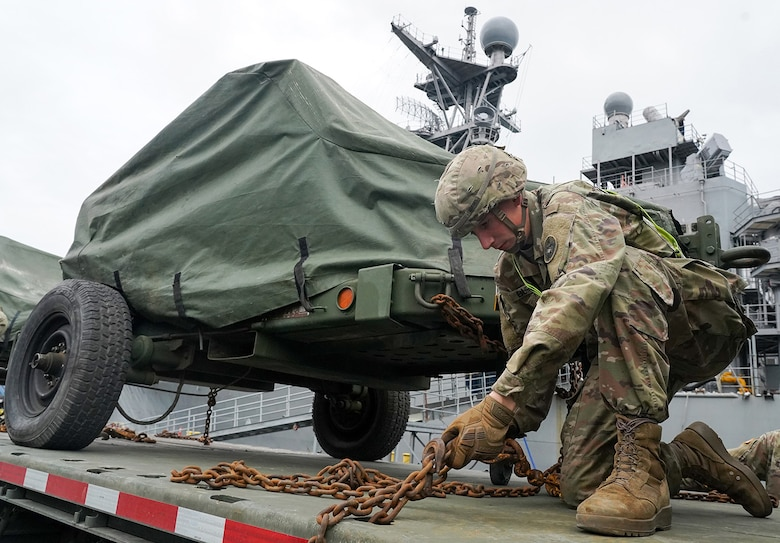 Specialist Timothy Burns, assigned to the 109th Transportation Company, 17th Combat Support Sustainment Battalion, U.S. Army Alaska, secures U.S. Marine Corps bulk fuel supplies and equipment from the U.S.S. Comstock (LSD-45), a Whidbey Island-class dock landing ship, to an M872 trailer at the port of Seward, Alaska, Sept. 19, 2019, for transport to Joint Base Elmendorf-Richardson, Alaska. The U.S. Navy is conducting an Arctic Expeditionary Capabilities Exercise to test its logistical effectiveness and joint-service interoperability while responding to conflict or disaster in an austere environment with no organic assets.
