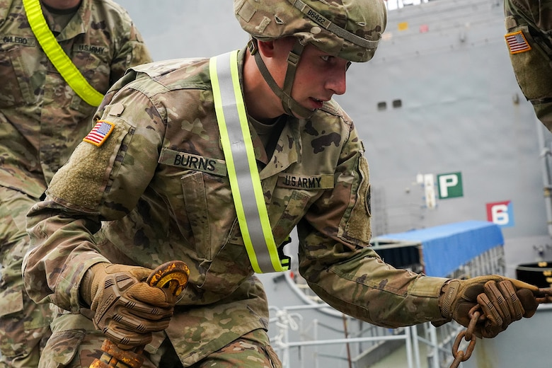 Specialist Timothy Burns, assigned to the 109th Transportation Company, 17th Combat Support Sustainment Battalion, U.S. Army Alaska, secures U.S. Marine Corps bulk fuel supplies and equipment from the U.S.S. Comstock (LSD-45), a Whidbey Island-class dock landing ship, at the port of Seward, Alaska, Sept. 19, 2019, for transport to Joint Base Elmendorf-Richardson, Alaska. The U.S. Navy is conducting an Arctic Expeditionary Capabilities Exercise to test its logistical effectiveness and joint-service interoperability while responding to conflict or disaster in an austere environment with no organic assets.