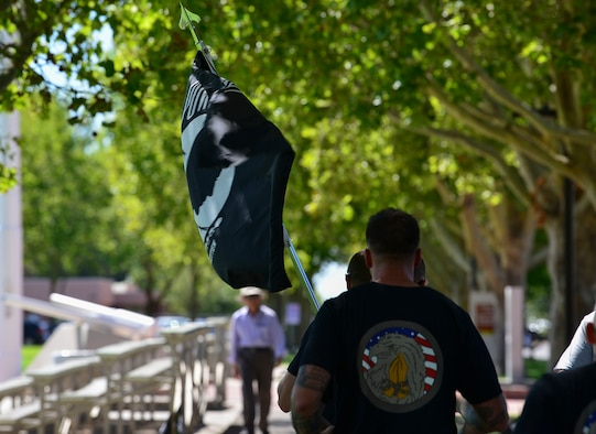 A Team Kirtland First Sergeant holds the POW/MIA flag during the 24-hour run or walk event at Kirtland Air Force Base, N.M., Sept. 19, 2019. After the 24 hours, a ceremony was hosted at the New Mexico Veterans Memorial Park where members of the community joined Team Kirtland to honor POW/MIAs. (U.S. Air Force photo by Senior Airman Enrique Barceló)
