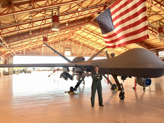 Capt. Cristina Kellenbence, a 2010 Academy graduate, poses next to an Air Force Remotely Piloted Aircraft that she pilots. (Courtesy photo)