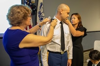 "U.S. Army Lt. Col. Patrick Bradley has his new rank pinned on by his wife and mother during his promotion ceremony at Joint Task Force Civil Support headquarters. The ceremony was presided over by Joint Task Force Civil Support Commanding General U.S. Army Maj. Gen. William ""Bill"" Hall, and was attended by Bradley's wife, his son and daughter and his parents. (Official DoD photo by Mass Communication Specialist 3rd Class Michael Redd/RELEASED)"