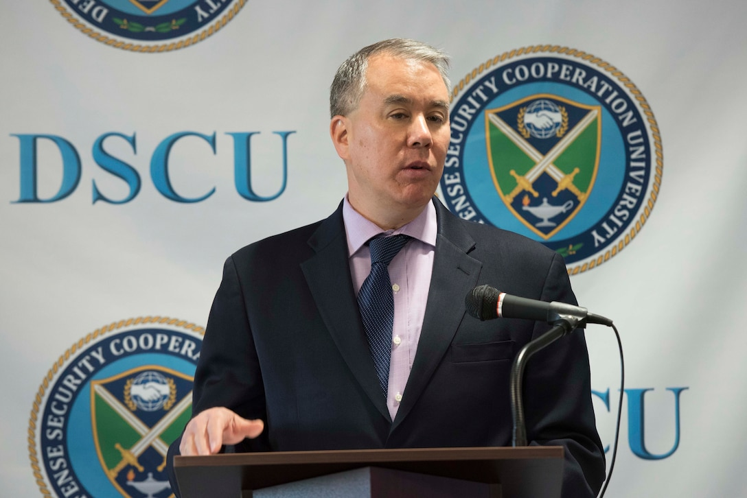 """A man speaks at a lectern. Behind him, the letters """"DSCU"""" and a logo are on a backdrop."""
