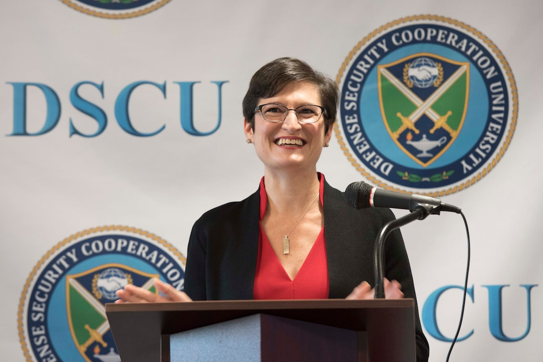 """A woman speaks at a lectern. Behind her, the letters """"DSCU"""" and a logo are on a backdrop."""