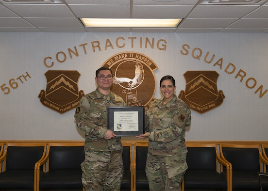 Tech. Sgt. Michael Jakubec, 56th CONS noncommissioned officer in charge of services flight, receives an unlimited contract warrant certificate from Maj. Barbara Divine, 56th Contracting Squadron commander, Sept. 26, 2019, at Luke Air Force Base, Ariz.