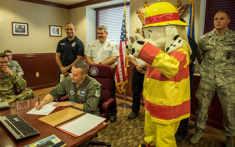 """Col Lee Gentile, 47th Flying Traiining Wing commander, signs the Fire Prevention Week Proclamation as Sparky gives the """"thumbs-up"""" Sept. 25, 2019 at Laughlin  Air Force Base, Texas. Gentile and base firefighters promoted the importance of fire saftey, as well as the upcoming FPW, which starts Oct. 7 - 11.  (U.S. Air Force photo by Master Sgt JT May III)"""