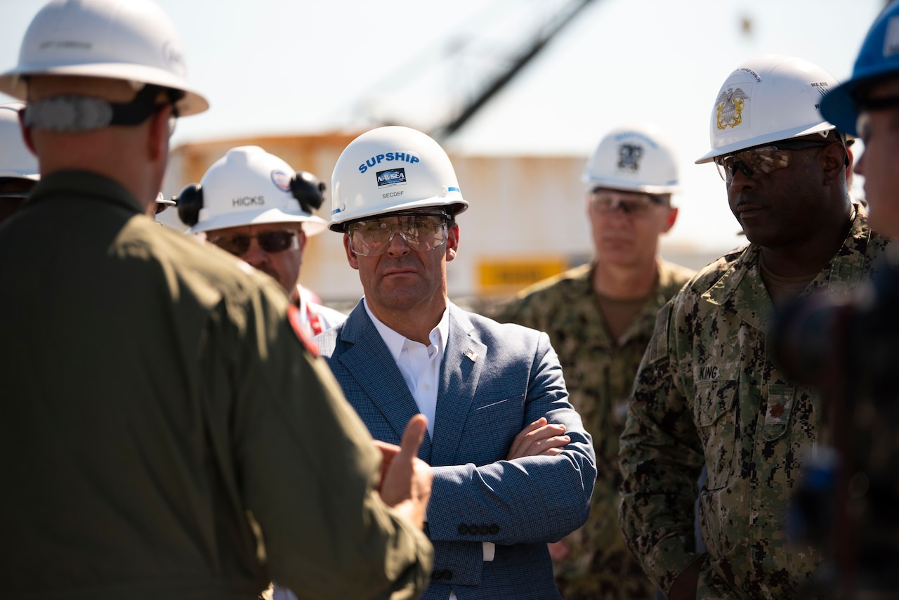 Man wearing hard hat and safety glasses listens to a man in a green uniform and hard hat, whose back is to the camera.