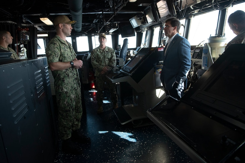 Aboard a ship, a man in a suit talks to a man dressed in fatigues as three other men look on.