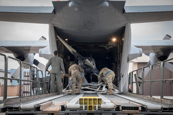 Photo of three military members removing equipment from a C-130.