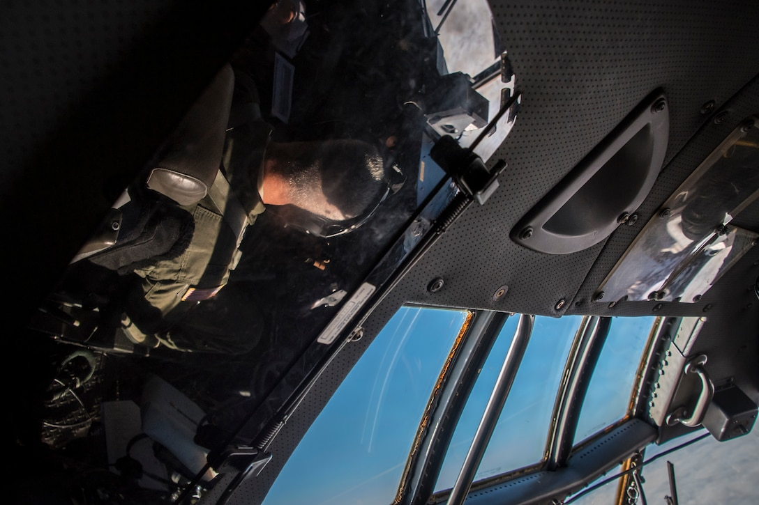 Abstract photo of the C-130 flight deck with pilot reflections in mirrors and windows.