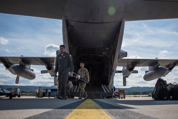 Photo of two military members carrying a medical stretcher from a C-130 on the flight line