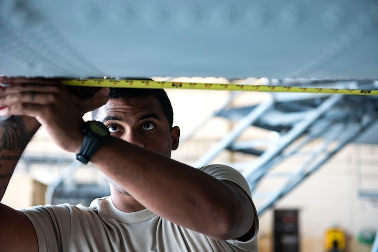 """Staff Sgt. Aaron Nazario, 71st Aircraft Maintenance Unit crew chief, measures the spacing for shorings during preparation of an HC-130J Combat King II for a situational awareness communication upgrade (SACU) modification Sept. 25, 2019, at Moody Air Force Base, Ga. The shorings allow the aircraft to be put into a state of no-loading"""", where the pressure and weight of the aircraft will be reduced, allowing the modifications to be implemented without damage to the aircraft's hull integrity. This SACU will enhance the aircraft's ability to communicate with personnel on the ground during search and rescue operations. (U.S. Air Force photo by Senior Airman Erick Requadt)"""