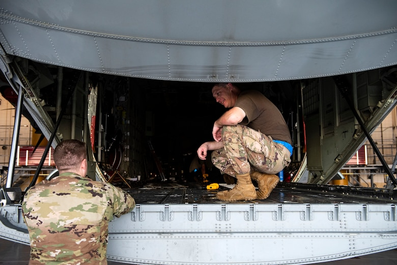 Tech. Sgt. Phillip Horton, right, 71st Aircraft Maintenance Unit (AMU) crew chief, speaks with 1st Lt. Derek Mundell, 71st AMU assistant officer in charge, during preparation of an HC-130J Combat King II for a situational awareness communication upgrade (SACU) modification Sept. 25, 2019, at Moody Air Force Base, Ga. This SACU will enhance the aircraft's ability to communicate with personnel on the ground during search and rescue operations. (U.S. Air Force photo by Senior Airman Erick Requadt)