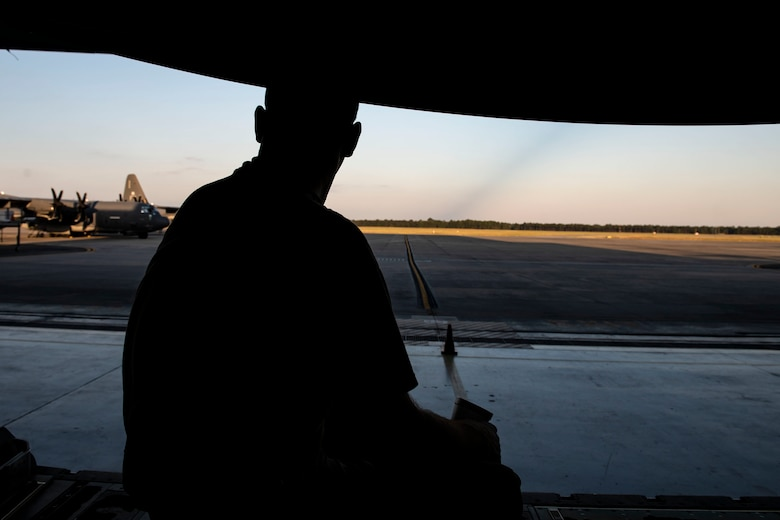 Tech. Sgt. Phillip Horton, 71st Aircraft Maintenance Unit crew chief, looks out onto the flightline after removing cargo floor panels during preparation of an HC-130J Combat King II for a situational awareness communication upgrade (SACU) modification Sept. 25, 2019, at Moody Air Force Base, Ga. The panels are removed to allow access to the area inside the aircraft where the SACU will be installed. This SACU will enhance the aircraft's ability to communicate with personnel on the ground during search and rescue operations. (U.S. Air Force photo by Senior Airman Erick Requadt)