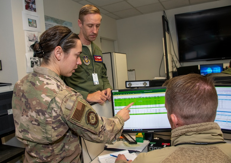 U.S. Air Capt. Lauren Allen, left, 321st Air Mobility Operations Squadron executive officer, Maj. Andreas Johnsen, center, 349th AMOS airlift control team chief and Tech. Sgt. Sam Caryl, 321st AMOS squadron requirements planner, study data files at the Weapons Systems Suite in the Air Operations Center during exercise Mobility Guardian Sept. 25, 2019, at Travis Air Force Base, California. MG19 is Air Mobility Command's flagship exercise for large-scale, rapid global mobility operations. Forty-six U.S. aircraft joined aircraft from 29 international partners, along with more than 4,000 U.S. and international Air Force, Army, Navy and Marine Corps aviators. (U.S. Air Force photo by Heide Couch)
