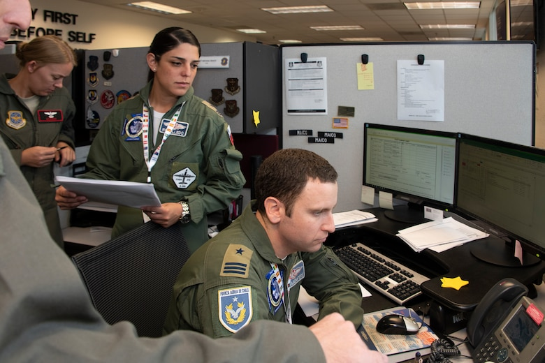 Chilean Air Force Capts. Romina Rebolledo, C-212 transport pilot and liaison  officer to the Brigade General and Felipe Casasempere, F-16 pilot and chief of planning for the 3rd Squadron, listen to a phone call during exercise Mobility Guardian Sept. 25, 2019, at Travis Air Force Base, California. MG19 is Air Mobility Command's full spectrum readiness exercise, designed to strengthen and improve integrated teamwork. U.S. aircraft joined aircraft from more than two dozen nations along with more than 4,000 U.S. and international Air Force, Army, Navy, and Marine Corps service members. (U.S. Air Force photo by Heide Couch)