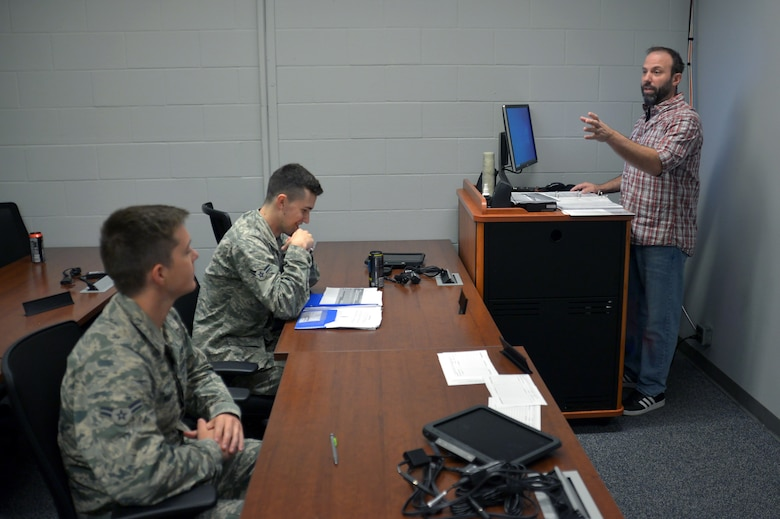 Darryl Ebsch, a civilian instructor, goes over radio frequency distribution with two Airmen assigned to the 55th Aircraft Maintenance Squadron.