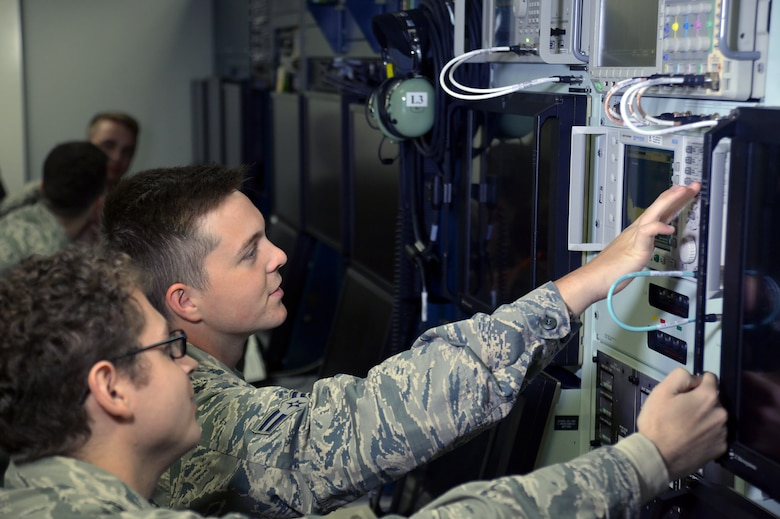 Two Airmen train on replica of an aircraft computer system.