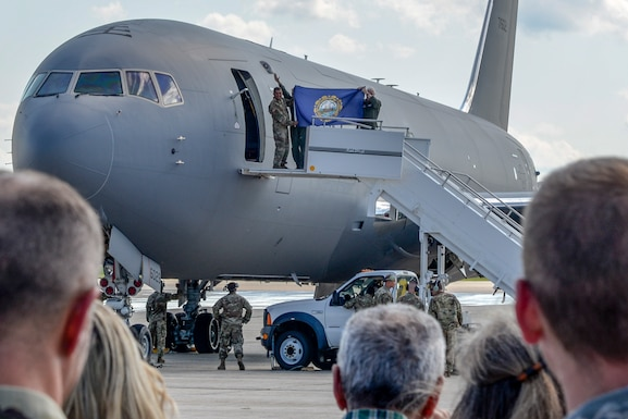 Lt. Gen. L. Scott Rice, Director of the Air National Guard, Maj. Gen. David Mikolaities, Adjutant General of New Hampshire, and Brig. Gen. Laurie Farris, Commander of the New Hampshire Air National Guard, hold up a NH state flag as they exit the first delivered KC-46 Pegasus to Pease Air National Guard Base, NH, Aug. 8, 2019. The Pegasus forges a new era at Pease marking the first upgrade to its aircraft inventory in decades.(U.S. Air National Guard photo by Senior Airman Taylor Queen)