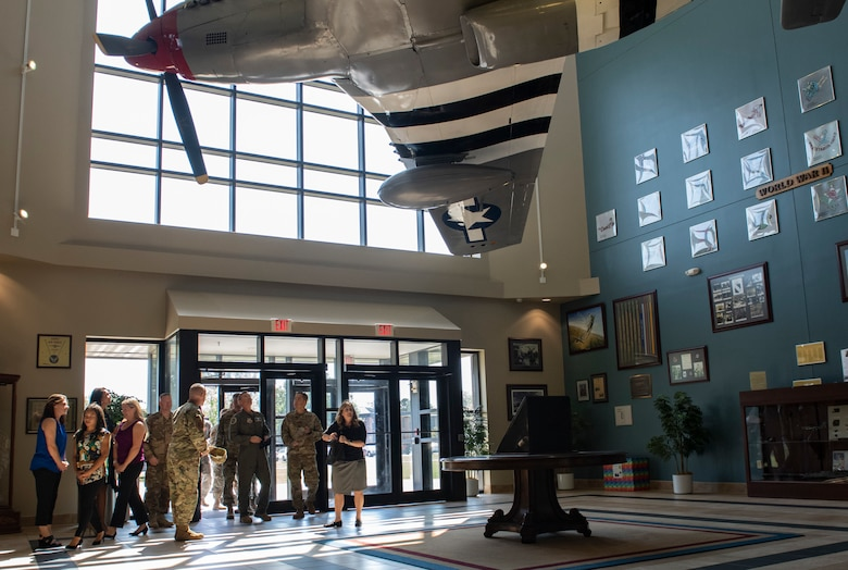 U.S. Air Force Maj. Gen. Chad Franks, Ninth Air Force commander, his delegation, and leaders from the 4th Fighter Wing enter the new 4th FW headquarters atrium at Seymour Johnson Air Force Base, N.C., Sept. 23, 2019. The atrium houses a P-51 Mustang and is decorated with memorabilia commemorating the Wings distinguished history. (U.S. Air Force photo by Senior Airman Kenneth Boyton)