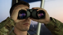 Senior Airman Hunter J. Maggard, 2nd Operations Support Squadron air traffic control apprentice, uses his binoculars to locate an aircraft on the flightline at Barksdale Air Force Base, Louisiana, August 22, 2019.