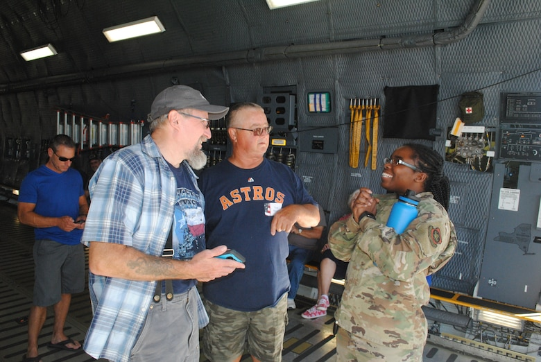 A maintenance Airman talks about a C-5M Super Galaxy to civilians and veterans inside the C-5M.