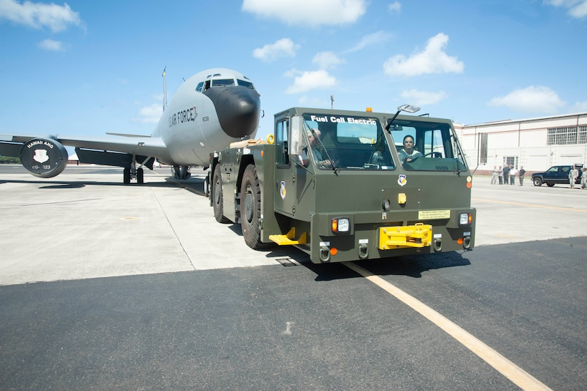"""A green flatbed tow vehicle with """"Fuel Cell Electric"""" written on the windshield pulls a large military transport jet."""