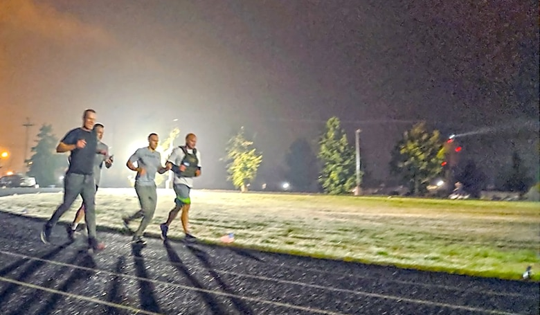 Members of the 225th Air Defense Squadron, lead by their commander Col. Brian Bergren (left), run during the early morning hours Sept. 19, 2019 during the POW/MIA Remembrance Run on Joint Base Lewis-McChord. (Courtesy photo)
