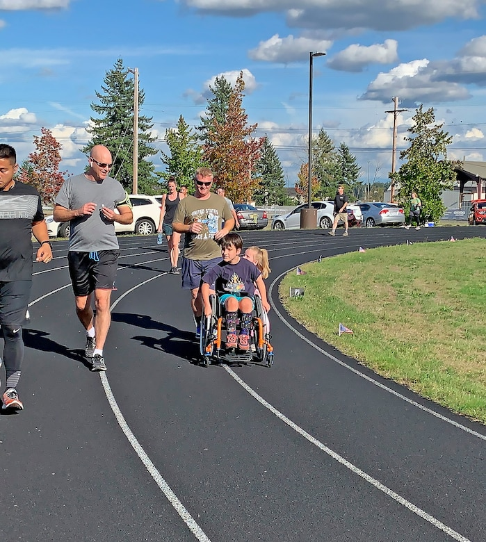 Col. Brett Bosselmann (left), 225th Support Squadron commander, runs with Master Sgt. Eric Poe and his children during the POW/MIA Remembrance Run Sept. 18, 2019 at Joint Base Lewis-McChord. (Courtesy photo).