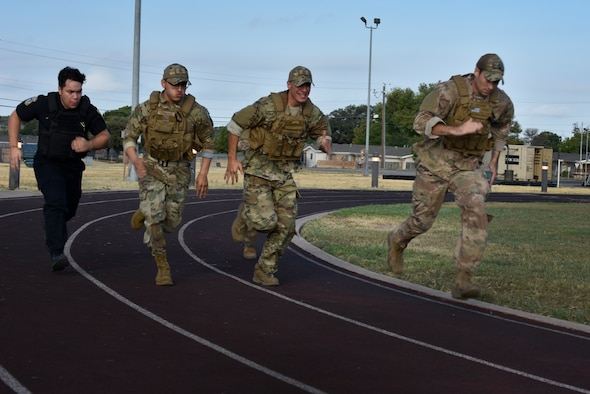 47th Security Forces Squadron Airmen begin phase two of tryouts for the San Antonio Basic Special Weapons and Tactics (SWAT) course by sprinting around the track at Laughlin Air Force Base, Texas, on Sept. 25, 2019. Phase one consisted of a physical fitness test with a twist: U.S. Army situps, release pushups and pullups. (U.S. Air Force photo by Senior Airman Anne McCready)