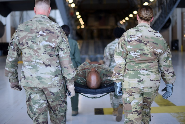 Chief Wright is carried in a stretcher by a group of four Airmen as they simulate evacuating injured people via the opened back hatch of a C-5M Super Galaxy