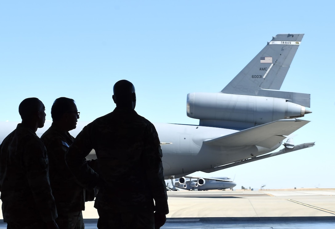 The forms of Chief Wright and two other Airmen are silhouetted against the bright light of the sun on the Travis flight line. Also pictured: the tail of a KC-10 Extender.