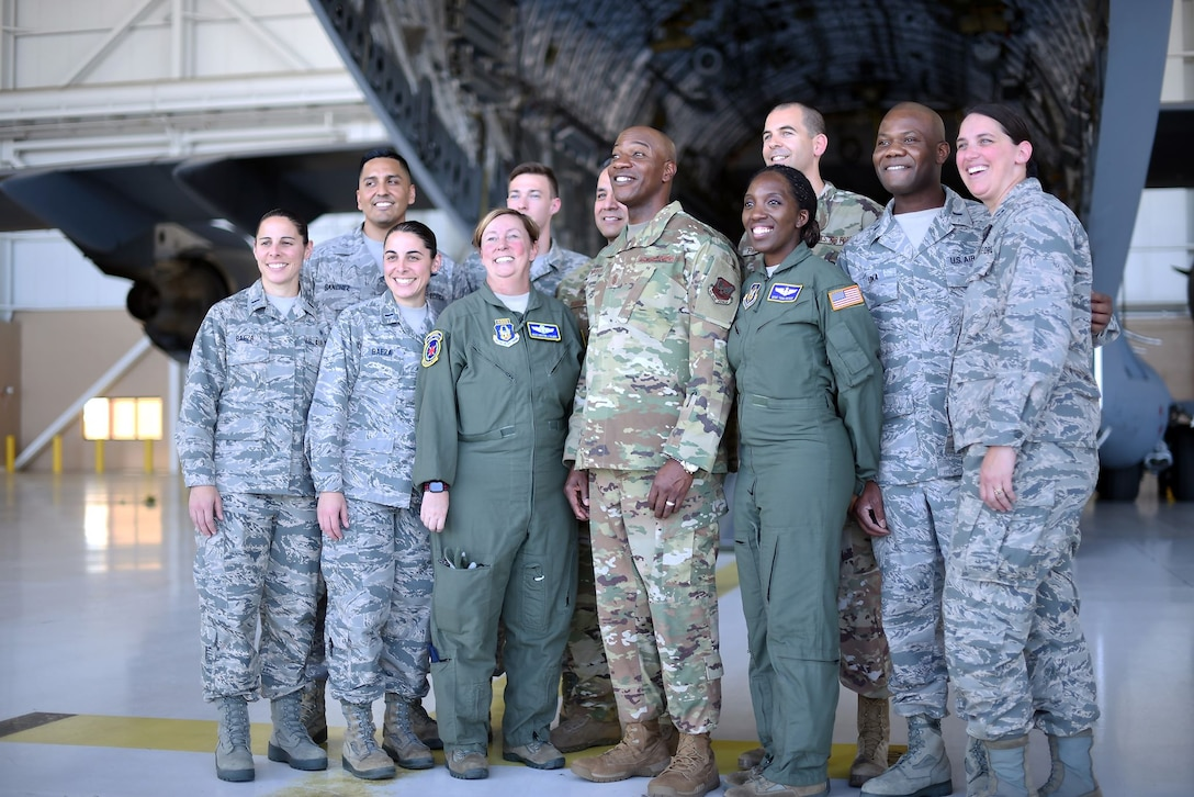 Chief Wright is surrounded by Airmen in an aircraft hangar. They're posing for a picture. They're smiling.