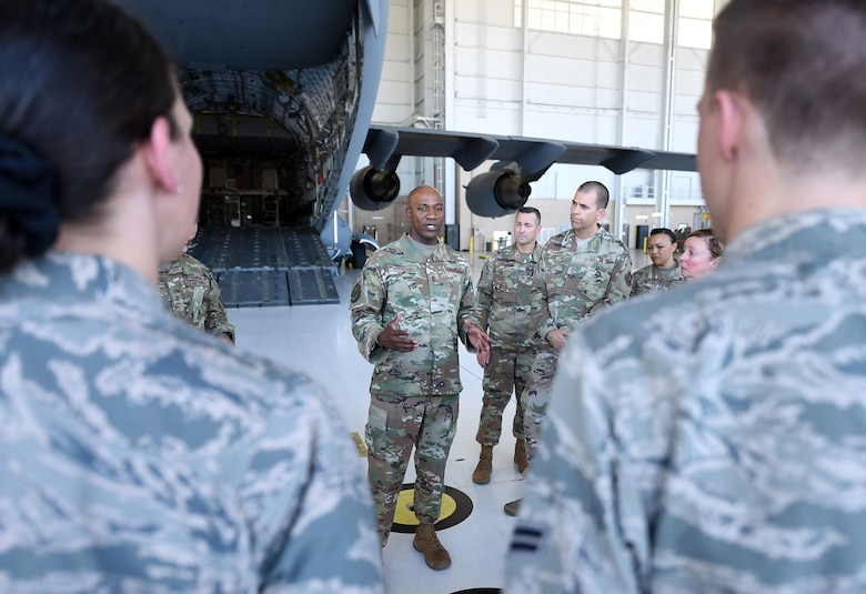 Chief Wright is surrounded by Airmen in an aircraft hangar. They're listening intently to what he's saying