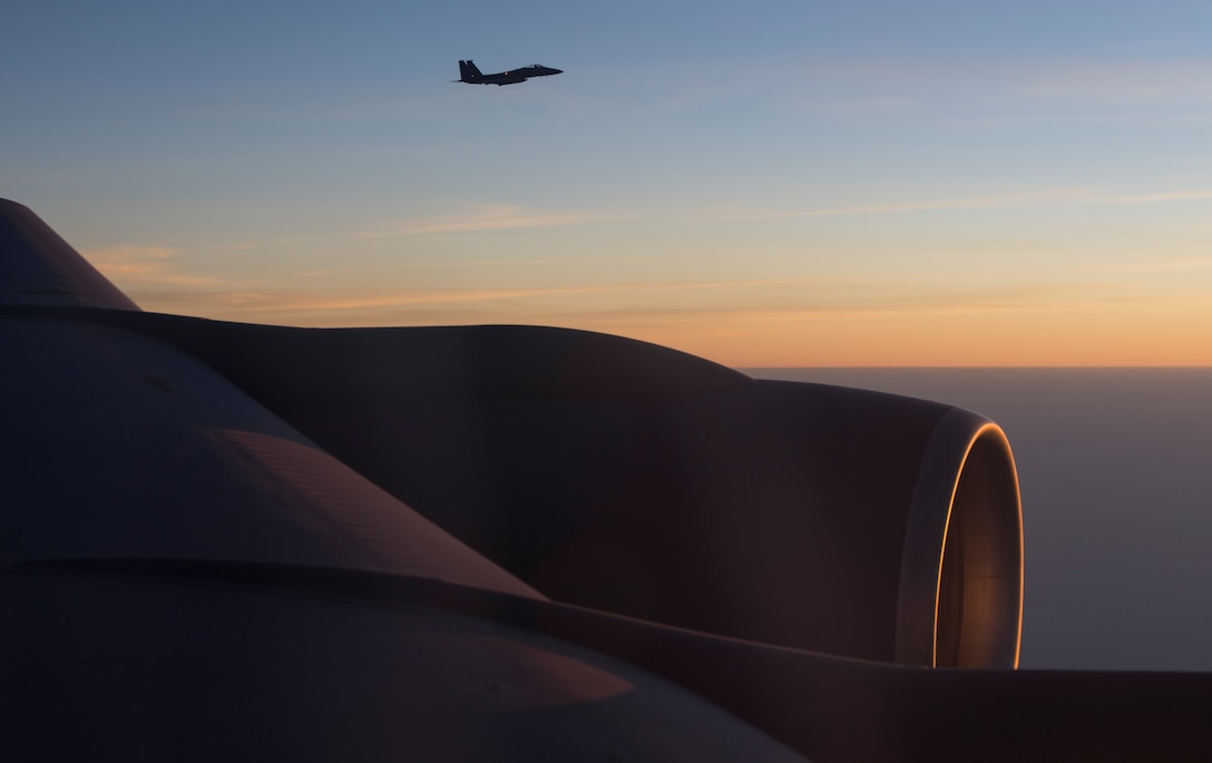 An F-15C Eagle flies near the wing of a KC-135 Stratotanker