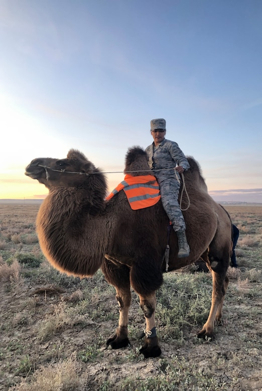"U.S. Air Force Senior Airman Liana Chythlook, assigned to the 176th Medical Group, Alaska Air National Guard, rides a Bactrian camel Sept. 20, 2019,  at a farm during Gobi Wolf 2019 in Sainshand, Mongolia. GW 19 was hosted by the Mongolian National Emergency Management Agency and Mongolian Armed Forces as part of the United States Army Pacific's humanitarian assistance and disaster relief ""Pacific Resilience"" series. (Courtesy photo/Released)"