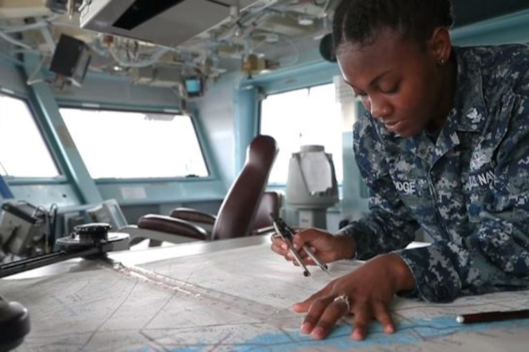 A sailor writes on a map on a table.