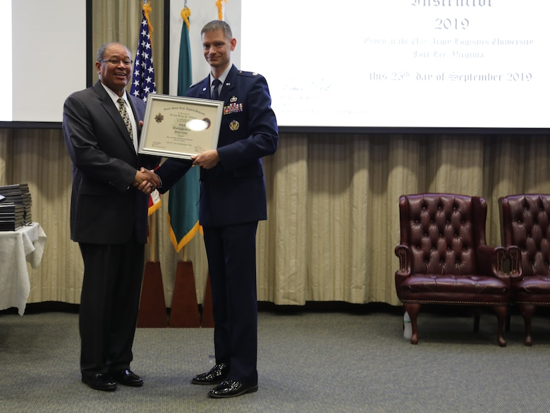 U.S. Air Force Lt. Col. Brian Wilken receives a 2019 Distinguished Instructor award from Michael Williams, Army Logistics University president during a ceremony at Fort Lee, Va., Sept. 25, 2019. Wilken is an instructor at the ALU College of Professional and Continuing Education, and earned the award for exceptional performance and significant achievements that greatly contributed to the success of ALU's academic and training mission. (U.S. Army photo / Dani Johnson)