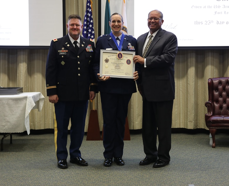 U.S. Air Force Lt. Col. Heather McDaniel receives the 2019 Educator of the Year award from Michael Williams, Army Logistics University president, during a ceremony at Fort Lee, Va., Sept. 25, 2019. McDaniel is an instructor at the ALU College of Professional and Continuing Education, and earned the award for her exceptional performance and significant achievements that greatly contributed to the success of ALU's academic and training mission. (U.S. Army photo / Dani Johnson)