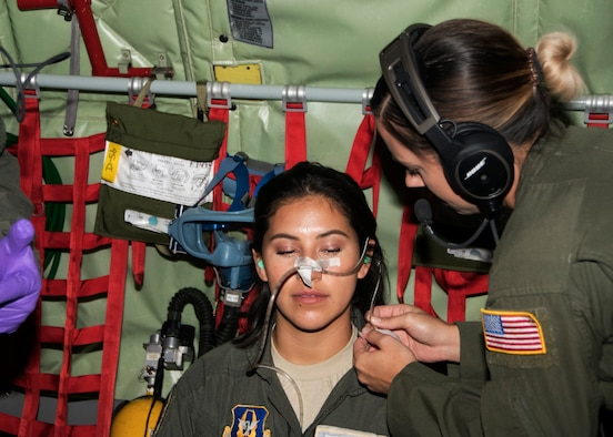 Master Sgt. Kat Hamblin, 459th Aeromedical Evacuation Squadron, shows a taping technique of a nasal gastric tube to protect its accidental removal on Senior Airman Maria Moposita during an off station trainer on a KC-135 Stratotanker, Sept. 20, 2019. The AES team conducted training during a flight to Wright Patterson, Ohio, where they later participated in the Air Force Marathon. (U.S. Air Force photo by Staff Sgt. Cierra Presentado/Released)