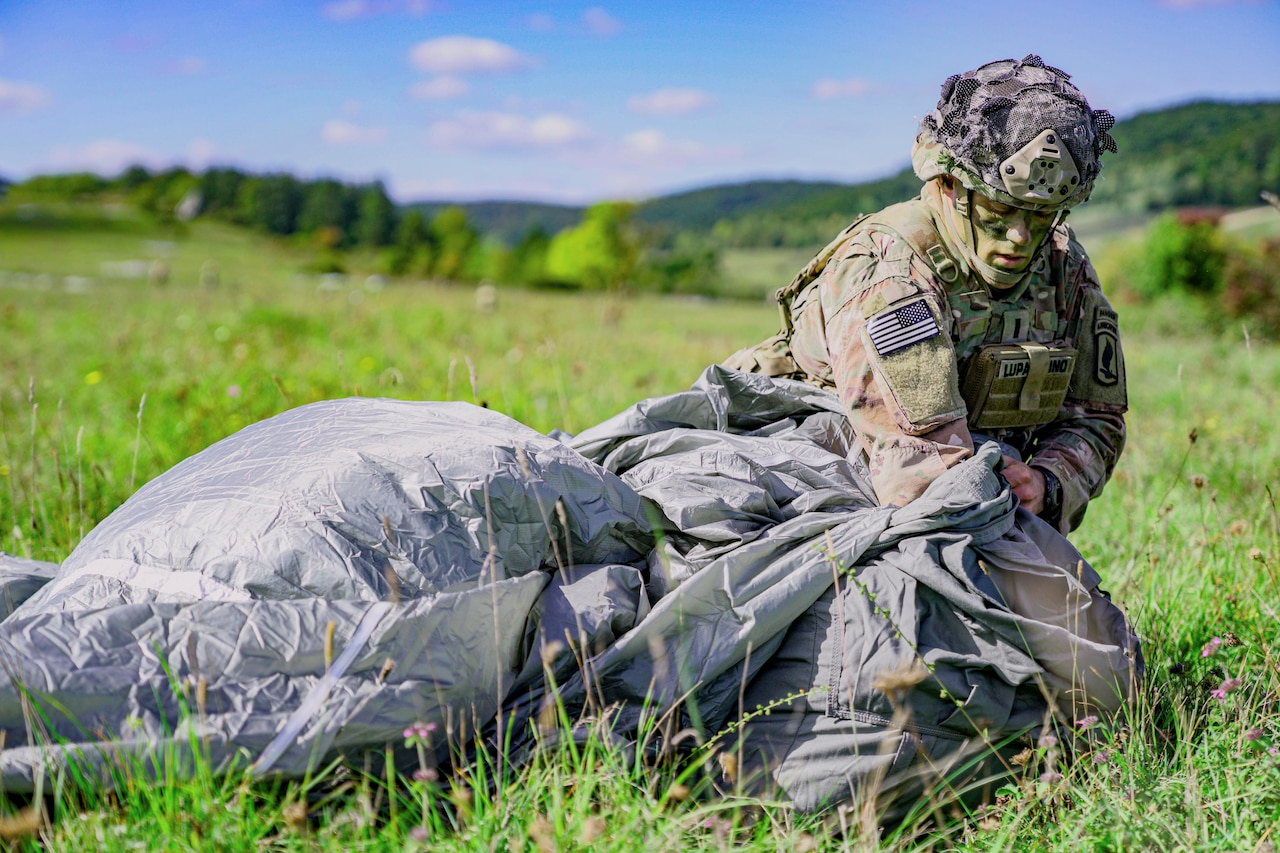 A soldier packs up a parachute.