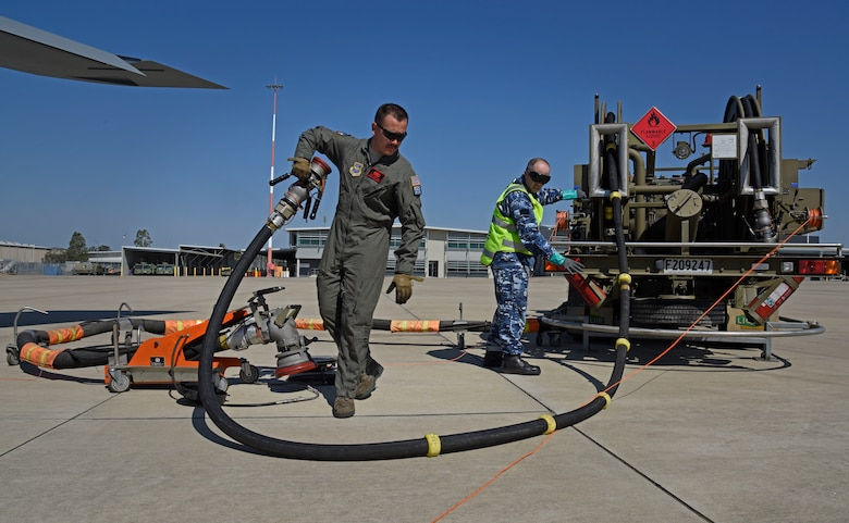 U.S. Air Force Staff Sgt. Austin Garcia, 92nd Aircraft Maintenance Squadron flying crew chief, and Royal Australian Air Force Sgt. Kane O'Connor, 23rd Squadron aircraft refueler, retract a fuel line during the first Airborne Warning and Control System World Tour at Royal Australian Air Force Amberley, Australia, Sept. 15, 2019.  Fairchild Air Force Base partnered with Tinker AFB during the AWACS world tour to maximize the E-3 Sentry flight time.  (U.S. Air Force photo by Senior Airman Jesenia Landaverde)