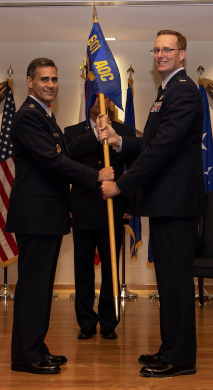Col. Greg Krane, 101st Air and Space Operations Group commander, takes the ceremonial flag from Lt. Gen. Marc Sasseville, Continental U.S. North American Aerospace Defense Command Region - First Air Force (Air Forces Northern) commander, during the 601st Air Operations Center change of command ceremony at Tyndall Air Force Base, Florida on Sept. 26, 2019. The passing of the flag symbolizes Krane's acceptance of command of the 601st AOC. (U.S. Air Force photo by Senior Airman Cheyenne Larkin)