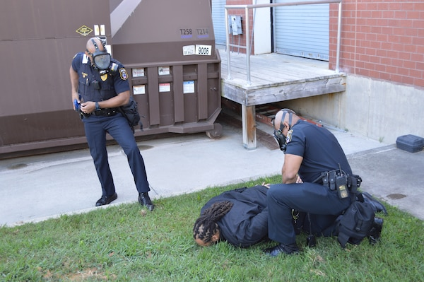 Two male police officers place another male under arrest during a simulated active shooter event.