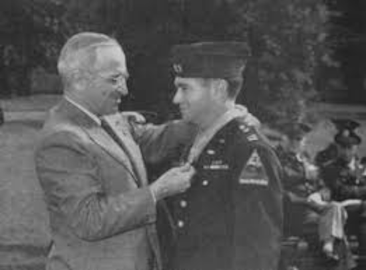 President Harry S. Truman places the Medal of Honor around the neck of Army Capt. James Burt.