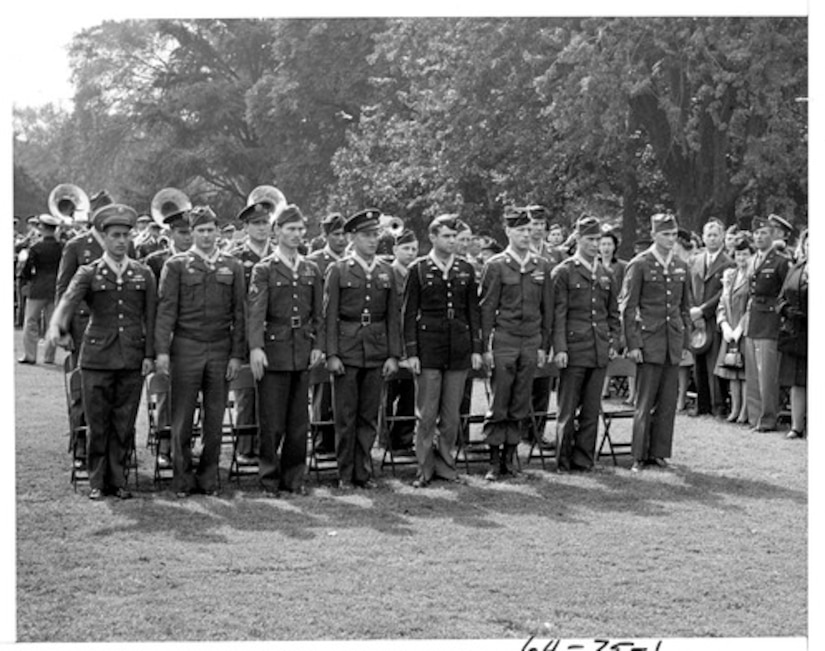 Two rows of eight soldiers stand at attention on the White House lawn wearing Medals of Honor.