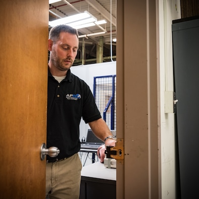 Dr. John McIntire, team lead and research psychologist in the Air Force Research Laboratory's 711th Human Performance Wing, demonstrates how to use one of the portable door locks his team developed. This team has been selected for a 2019 Defense Innovation Award. (U.S. Air Force photo by Richard Eldridge)